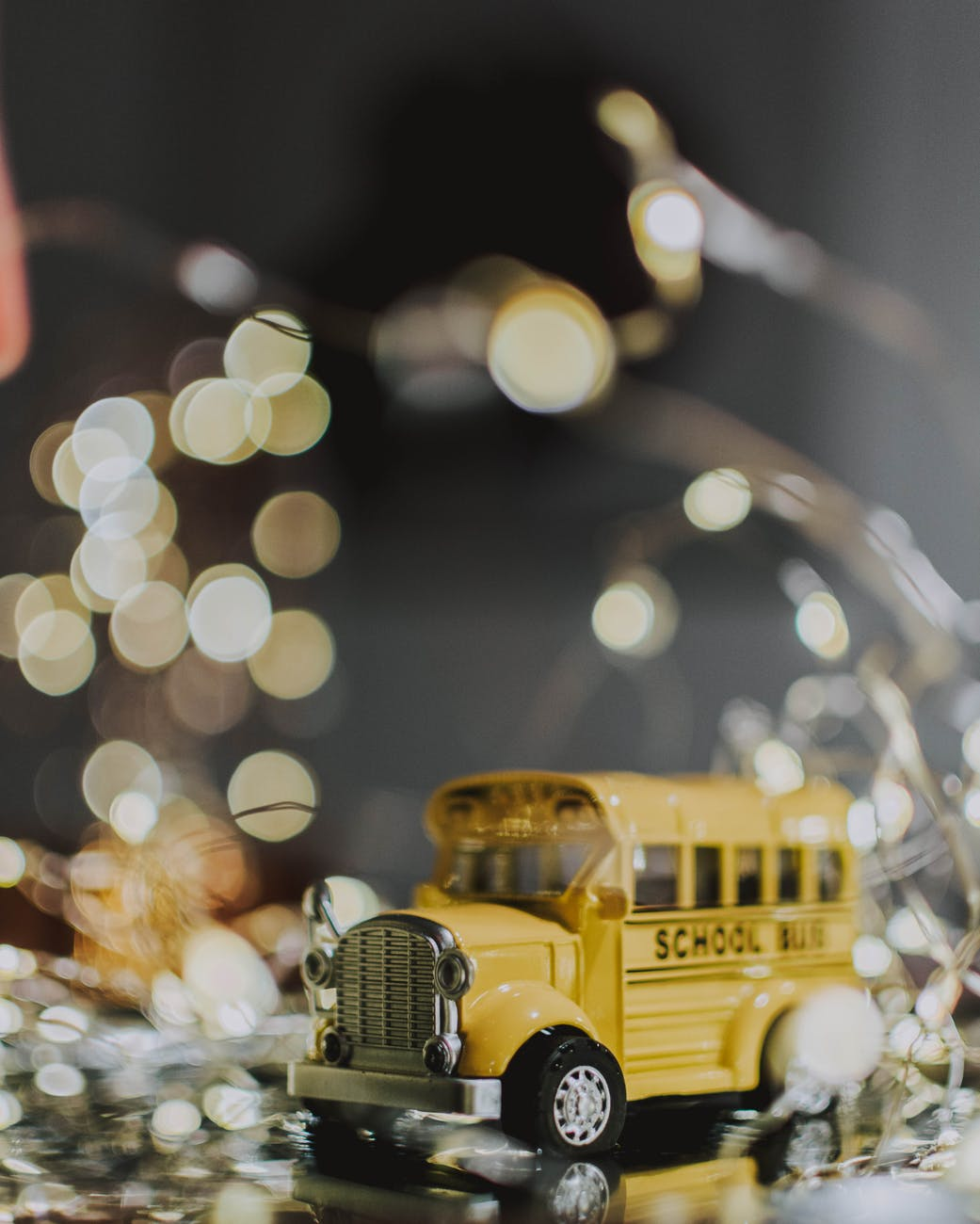 yellow school bus toy with light reflections